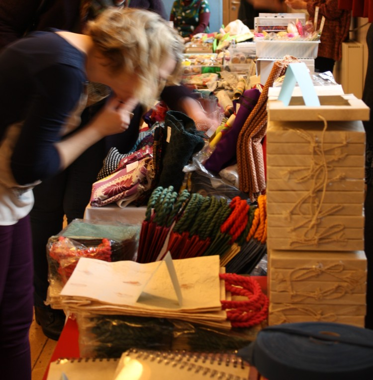 A customer browses a stall of crafting materials.