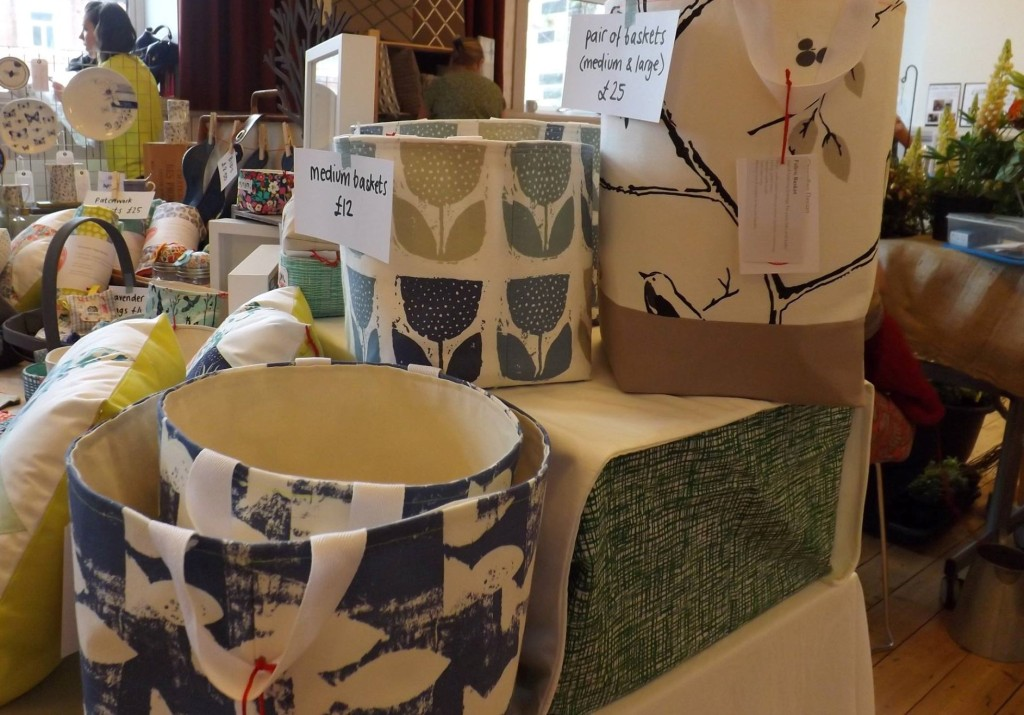 A craft fair stall featuring individually priced soft furnishings and homewares.
