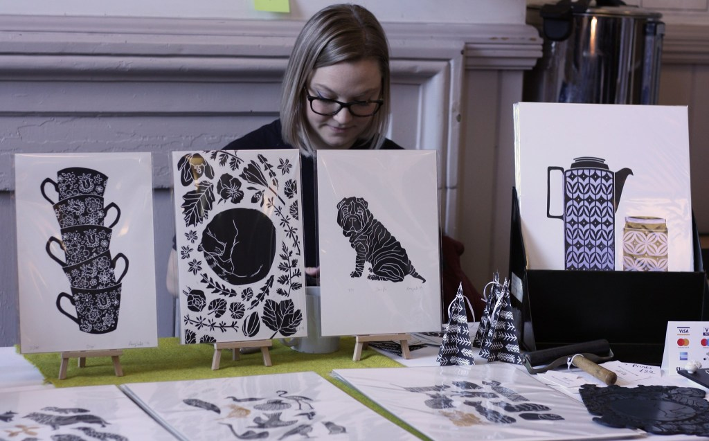 Artist sits behind her stall of prints.